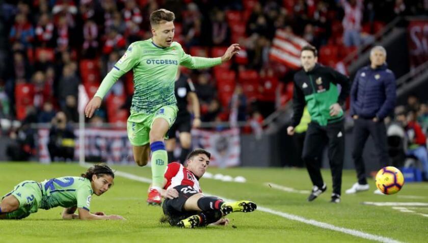 El jugador del Athletic de Bilbao Capa (d) despeja un balón ante Francis (c) y Diego Laínez, ambos del Real Betis, durante el partido de Liga en Primera División que se disputó este domingo en el estadio de San Mamés, en Bilbao. EFE