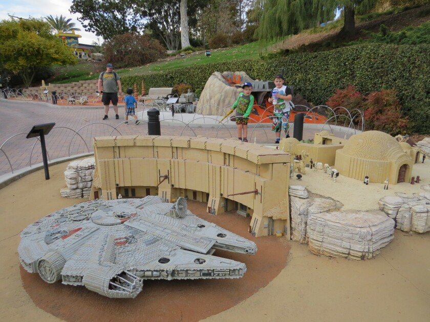 Boys admire the Tatooine display, including the Millennium Falcon ship in the foreground, at Legoland California theme park in Carlsbad on Nov. 18. The Star Wars Miniland attraction will close Jan. 6, 2020.