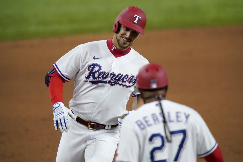 Texas Rangers' Nate Lowe, left, rounds third and is congratulated by third base coach Tony Beasley (27) after hitting a two-run home run against the Toronto Blue Jays during the first inning of a baseball game in Arlington, Texas, Tuesday, April 6, 2021. (AP Photo/Tony Gutierrez)