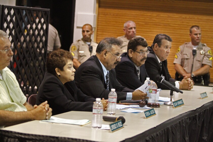 Los Angeles County Sheriff deputies stand near the Bell City Council during a meeting filled with angry citizens upset with the high salaries paid to the members.