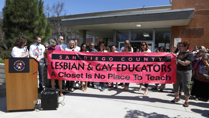 San Diego Unified administrators, board members and community members stand behind the banner that San Diego area educators carried during their debut appearance 25 years ago in the city's annual pride parade.