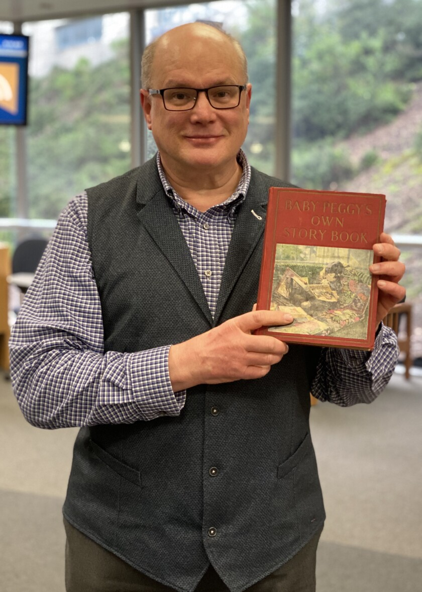 UCSD Geisel Library events and exhibits coordinator Scott Paulson holds one of his treasured Baby Peggy books.