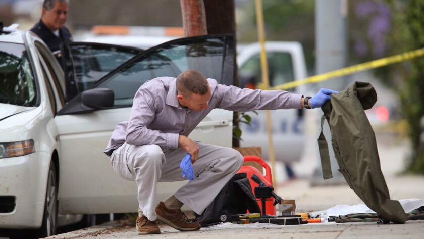 Authorities investigate the scene along 11th Street in Santa Monica, where a car was found with weapons, ammunition and other suspicious items.