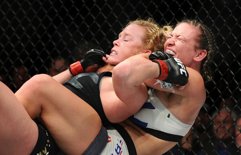 Miesha Tate sinks the chokehold on Holly Holm that led to a submission in the fifth round of their women's bantamweight championship fight at UFC 196 on Saturday night in Las Vegas.