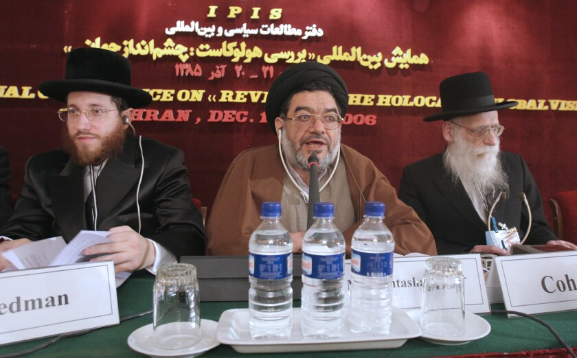 FILE— In this Dec. 11, 2006, file photo, top cleric Ali Akbar Mohtashamipour, center, speaks during a conference on the Holocaust with Rabbi Moishe Arye Friedman, left, from Austria, and Rabbi Ahron Cohen, right, from England, in Tehran, Iran. Mohtashamipour, a Shiite cleric who as Iran's ambassador to Syria helped found the Lebanese militant group Hezbollah and lost his right hand to a book bombing reportedly carried out by Israel, died Monday, June 7, 2021, of the coronavirus. (AP Photo/Vahid Salemi, File)