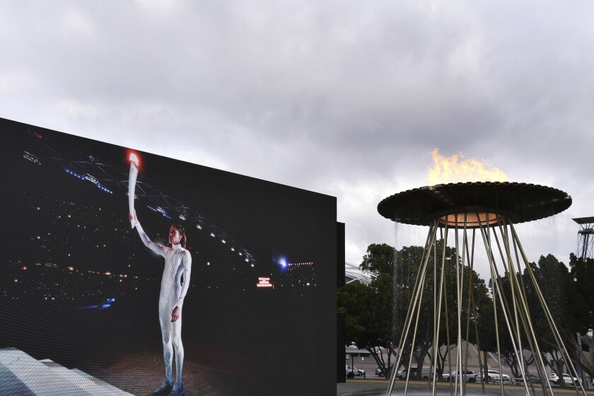 """A video screen shows Cathy Freeman lighting the Olympic Cauldron as part of the 20th anniversary celebrations of the Sydney 2000 Olympic Games in Sydney, Tuesday, Sept. 15, 2020. Freeman, who lit the cauldron at the original opening ceremony and won the 400-meter race at the track in one of the country's all-time great sporting moments, said it was a wonderful gesture to have """"two future stars"""" recognized on such a major stage ahead of the rescheduled 2020 Games in Tokyo next year. (Dean Lewins/AAP Image via AP)"""