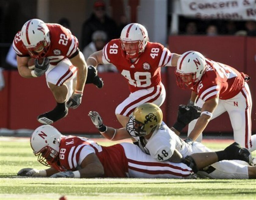 Nebraska running back Rex Burkhead (22) leaps over teammate, offensive linesman Keith Williams (68), with Kyler Reed (25) and Tyler Legate (48), as Colorado linebacker Liloa Nobriga (48) is on the ground, during the first half of an NCAA college football game, in Lincoln, Neb., Friday, Nov. 26, 201
