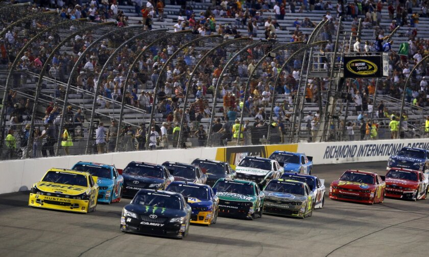 Kyle Busch (54) and Ryan Blaney (22) lead the field at the start of the NASCAR Nationwide series race at Richmond International Raceway in Richmond, Va., Friday, Sept. 5, 2014. (AP Photo/Steve Helber)