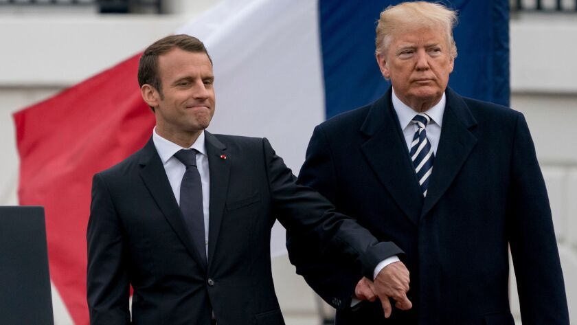 President Trump and French President Emmanuel Macron hold hands on the South Lawn of the White House in April 2018.