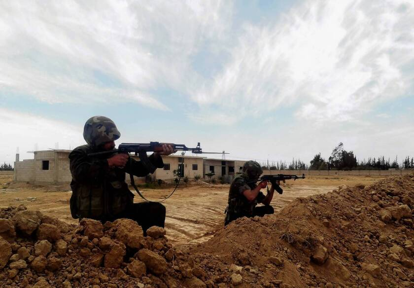 Syrian soldiers aim their weapons in Otaiba, east of Damascus. The government reportedly has seized the key supply hub of rebels.