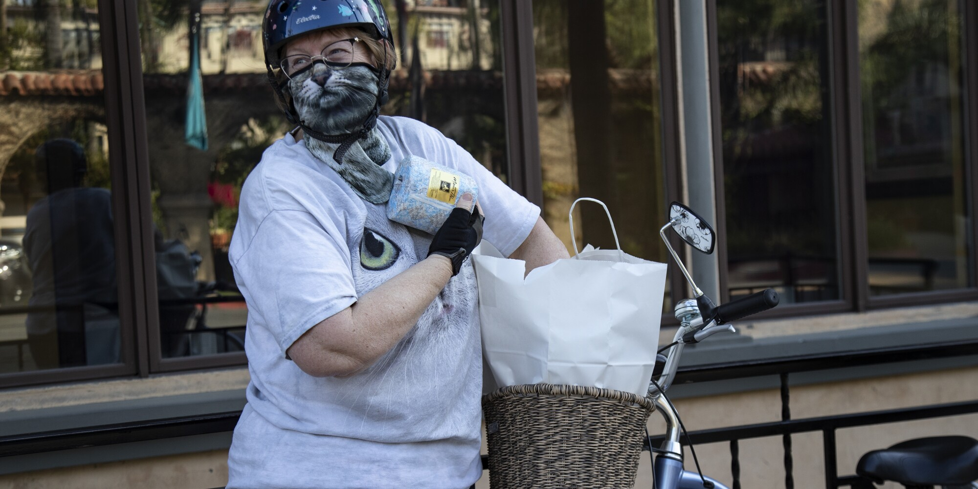A woman wearing a cat mask picks up takeout in Riverside