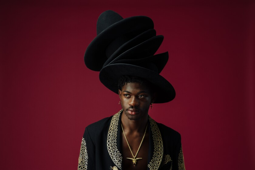Lil Nas X wears a stack of hats on his head