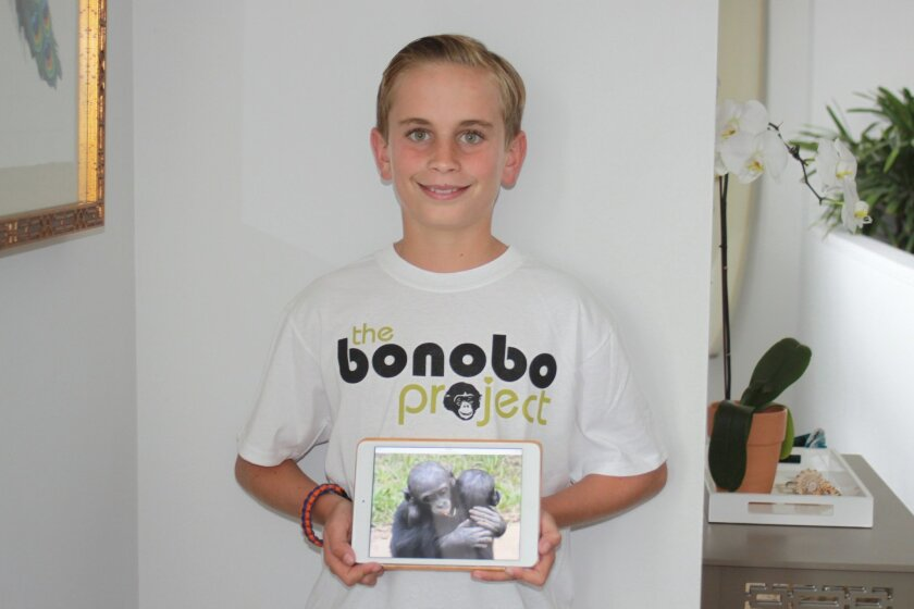 All hallows Academy fourth-grader Alex Goldman with his favorite picture of bonobo apes