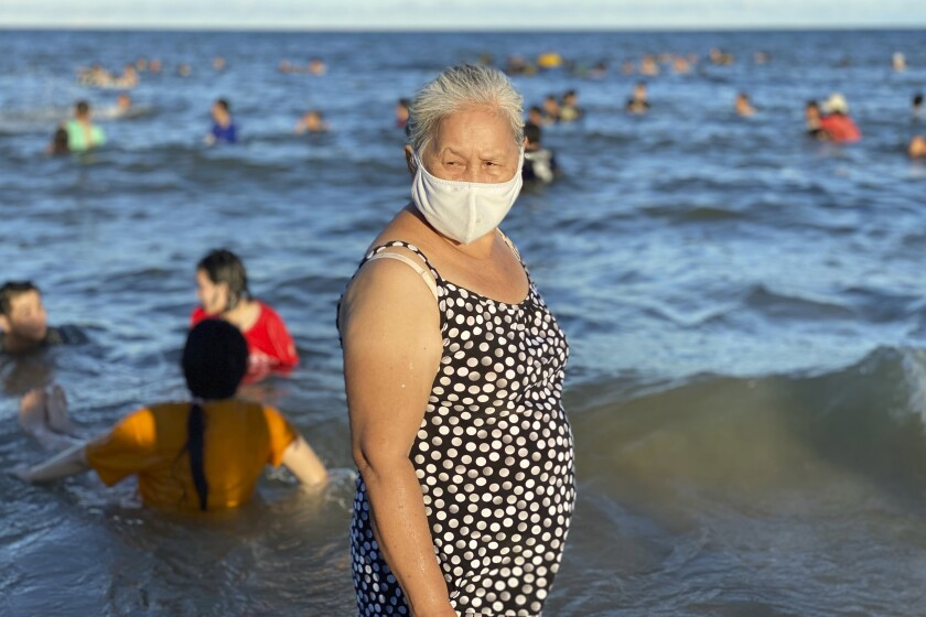 A woman stands on a beach in the city of Vung Tau in Vietnam.