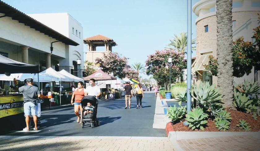 A few customers stroll the Otay Ranch Farmers Market on a Tuesday summer evening at Otay Ranch Town Center.