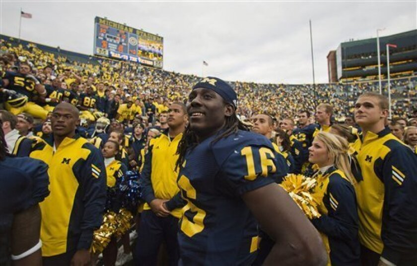 Michigan quarterback Denard Robinson (16) smiles he celebrates with teammates after an NCAA college football game against Connecticut, Saturday, Sept. 4, 2010, in Ann Arbor. Michigan won 30-10. (AP Photo/Tony Ding)