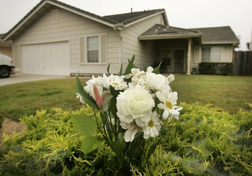 A bouquet of flowers is in front of the home on Via Metates in Oceanside Tuesday morning. The bodies of a 56-year-old man and his 52-year-old sister, along with a family dog were found dead in the home Monday, in an apparent murder-suicide.