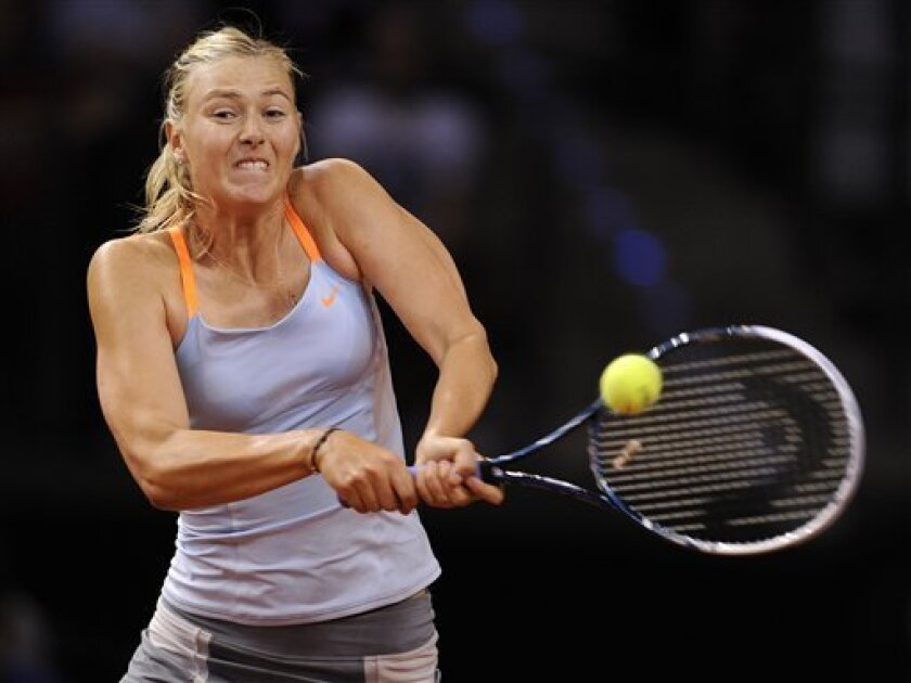 Russia's Maria Sharapova returns a shot to Serbia's Ana Ivanovic during their quarter final match at the Porsche tennis GP in Stuttgart, Germany, Friday, April 26, 2013. Sharapova won the match with 7-5,4-6 and 6-4. (AP Photo/dpa, Daniel Maurer)