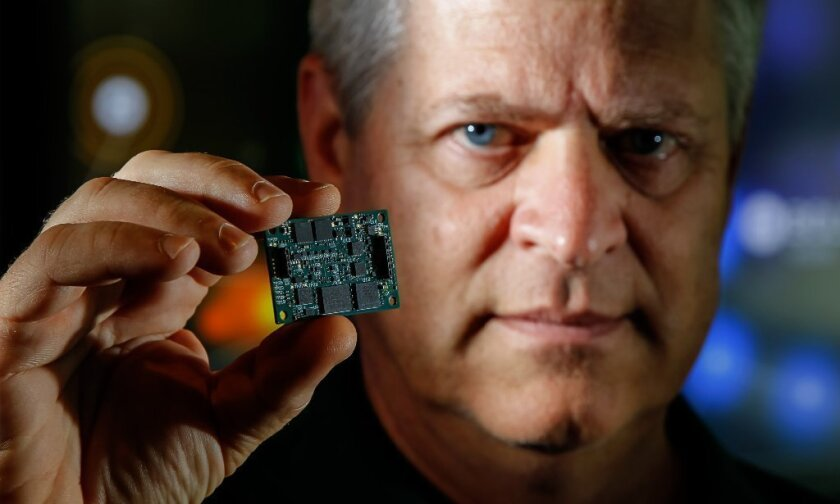 Jerry Goodwin, chief operating officer of ViaSat's Government Services Division, hold an embedded encryption card at the company's Carlsbad headquarters.