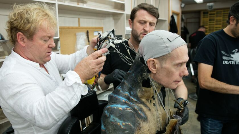 """Shane Mahan, left, and Mike Hill fitting the servos into the spine that controls the neck gill movements. The mechanics were hidden inside the creature's (Doug Jones) """"mantra ray"""" back anatomy."""