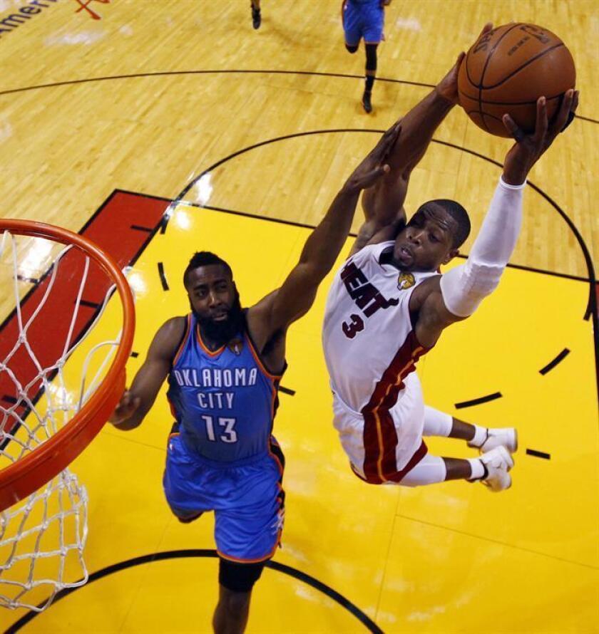 El jugador de Miami Heat Dwyane Wade (d) salta para encestar sobre el jugador James Harden. EFE/Archivo