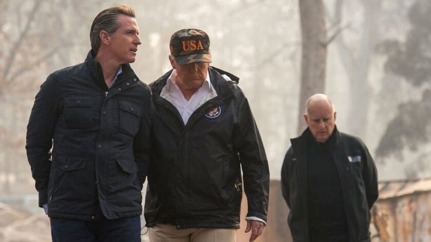 President Trump talks to then-Governor-elect Gavin Newsom during a visit on Nov. 17 to a Paradise neighborhood destroyed in the Camp fire. At right is then-Gov. Jerry Brown.