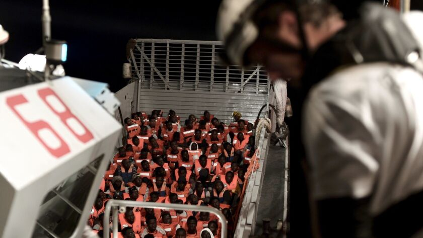 A handout photo made available by the NGO SOS Mediterranee shows the sea rescue of 629 migrants who were taken to the Aquarius boat.