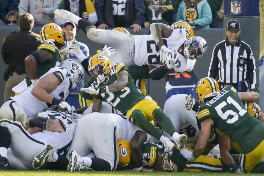 Raiders running back Josh Jacobs tries leaping his way to a first down, but the Packers eventually held him short of the mark.