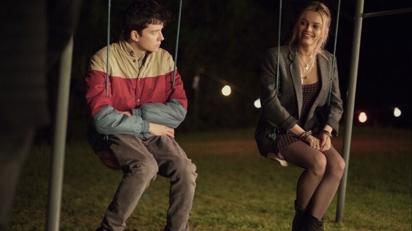 "This image released by Netflix shows Asa Butterfield, left, and Emma Mackey in a scene from ""Sex Edu"