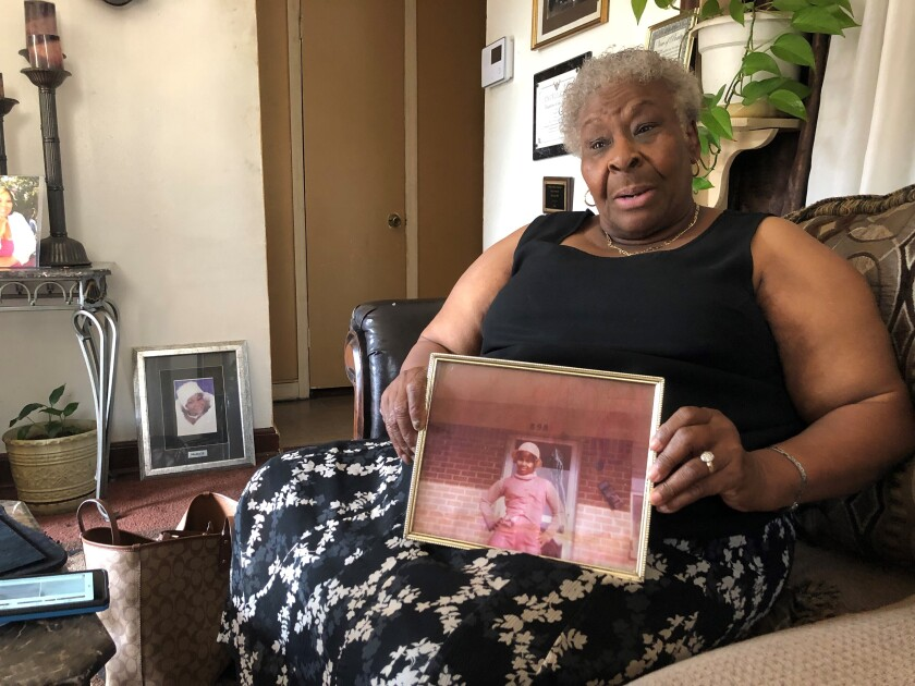 """Minnie Hill holds a photo of her late daughter, Rosie Hill, as she speaks to a reporter in her home on Thursday, Oct. 10, 2019 in Memphis, Tenn. Rosie Hill was found dead in Florida in 1982. In 2018, after Texas authorities began tying Samuel Little to murders around the country, Marion County, Fla., Sheriff's Detective Sgt. Michael Mongeluzzo joined police from several states who flew to a Texas prison, where Little was temporarily being held, in efforts to bring closure for their cold cases. The sheriff's office said """"Little confessed to killing Rosie Hill and dumping her body,"""" and even """"told Sgt. Mongeluzzo that he killed Rosie because God put him on this earth to do it."""" (AP Photo/Adrian Sainz)"""