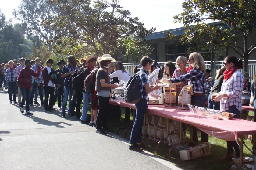 Parents serve sandwiches, beans, chips, waters and cookies for Muirlands Middle School's Western BBQ on Dec. 20, 2018.