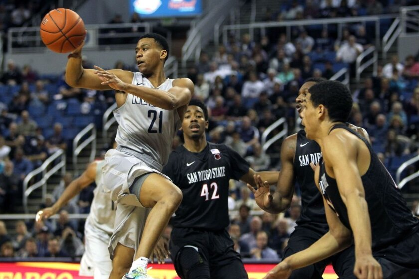 Nevada's Eric Cooper Jr. (21) passes against Jeremy Hemsley, Skylar Spencer and Trey Kell in SDSU's 57-54 victory.