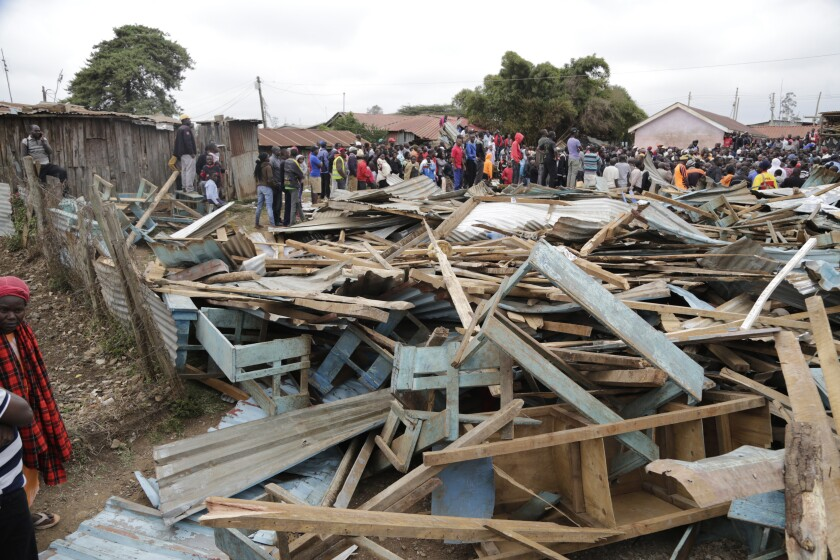 People and rescuers walk on debris of The Precious Talent Top School in Nairobi, Kenya, Monday, Sept. 23, 2019. The school collapsed in Kenya's capital on Monday morning, and officials said at least seven children were killed. Two others were critical condition. (AP Photo/Khalil Senosi)