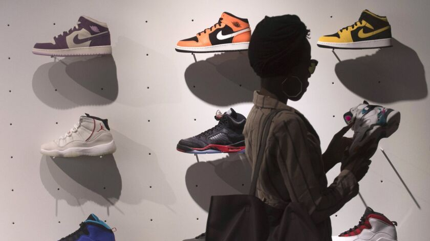 The explosive popularity of basketball sneakers and the rise of resale websites have turned shoes into an asset that can be sold like Wall Street securities. Here, a shopper examines a wall of Nikes at the Jumpman LA store in downtown Los Angeles.