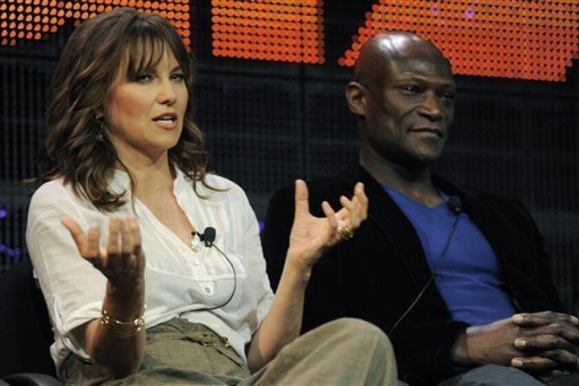 """Lucy Lawless, left, and Peter Mensah, cast members in the television series """"Spartacus: Gods of the Arena,"""" take part in a panel discussion during the Starz Networks Television Critics Association winter press tour in Pasadena, Calif., Friday, Jan. 7, 2011. (AP Photo/Chris Pizzello)"""