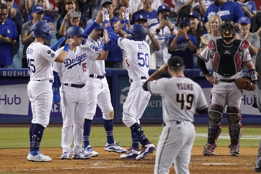 Los Angeles Dodgers' Mookie Betts, third from right, is congratulated by Matt Beaty, left, Austin Barnes, second from left, and AJ Pollock, third from left, after hitting a grand slam as Arizona Diamondbacks starting pitcher Alex Young, second from right, watches along with catcher Bryan Holaday during the seventh inning of a baseball game Saturday, July 10, 2021, in Los Angeles. (AP Photo/Mark J. Terrill)