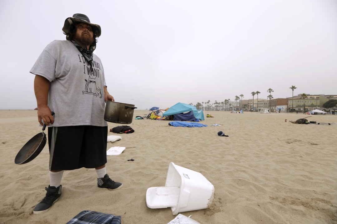 Kenny Carpenter, 34, collects his belongings before sanitation crews arrived in Venice
