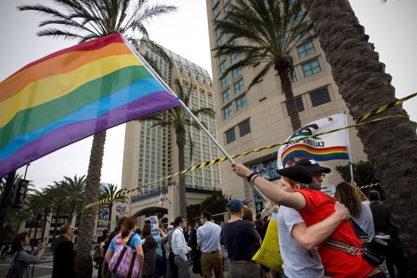Sean Bohac (left) and Kelsey Hoffman greeted each other after meeting at the rally yesterday outside the Manchester Grand Hyatt Hotel on Harbor Drive. Gay-rights groups are boycotting the hotel.