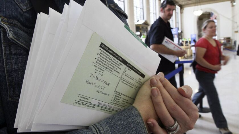 Denise Schiller, of New York, foreground, holds her taxes as she waits to send them out certified ma