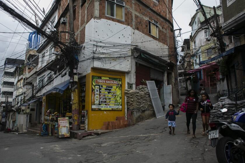 Unos residentes caminan frente a un edificio con orificios de bala días después de un operativo de la policía en la favela de Jacarezinho, en Río de Janeiro, Brasil, el sábado 8 de mayo de 2021. (AP Foto/Bruna Prado)