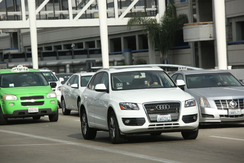 A car bearing an Uber emblem leaves LAX's departure area in July.