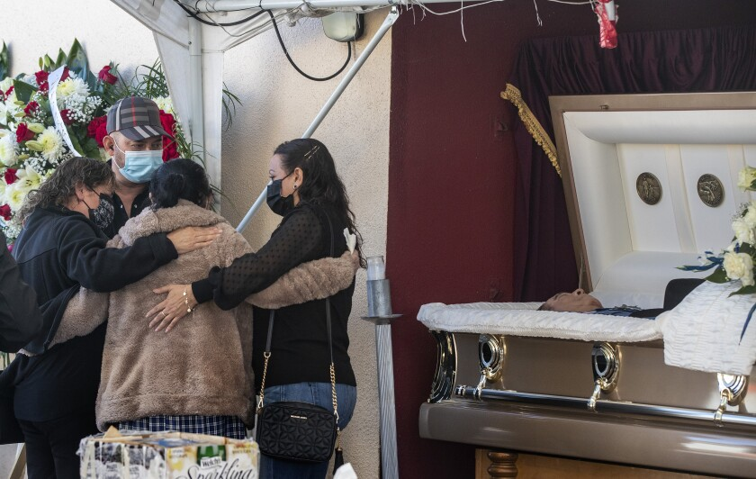Family and friends console one another as they gather at a service for Julio Aguilar on Dec. 20 in East Los Angeles.