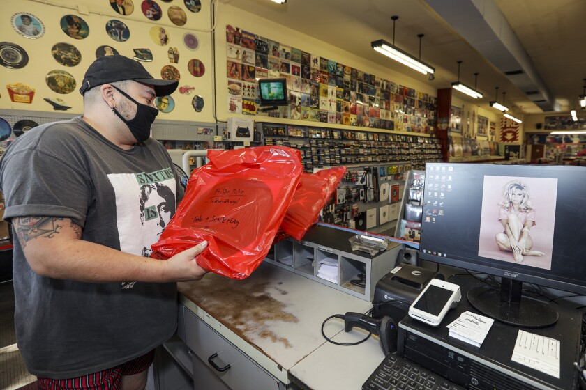Ruben Cortez, manager, with some online orders that are ready to be picked by customers at Lovell's Records in Whittier.