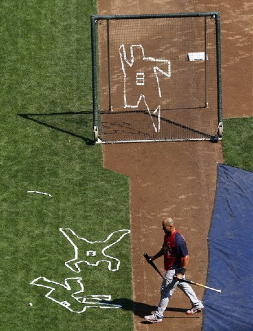 St. Louis Cardinals' Albert Pujols walks past outlines depicting Milwaukee Brewers' Ryan Braun falling down trying for an inside the park home run during last night's game during batting practice before a baseball game Thursday, Sept. 1, 2011, in Milwaukee. (AP Photo/Jeffrey Phelps)
