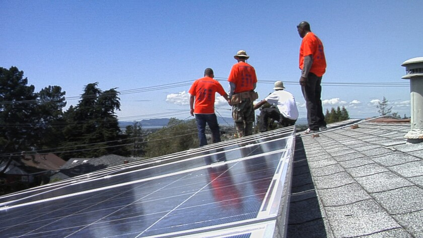 """Workers install solar panels in the documentary movie """"Catching the Sun,"""" by director Shalini Kantayya."""