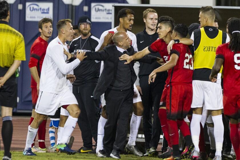 SDSU head coach Lev Kirshner holds SDSU's Matt Callahan away from UNLV's Jordan Chavez during a scuffle in the first half.