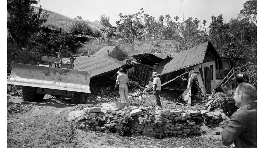 A bulldozer razes the Aréchigas' family home on May 8, 1959.