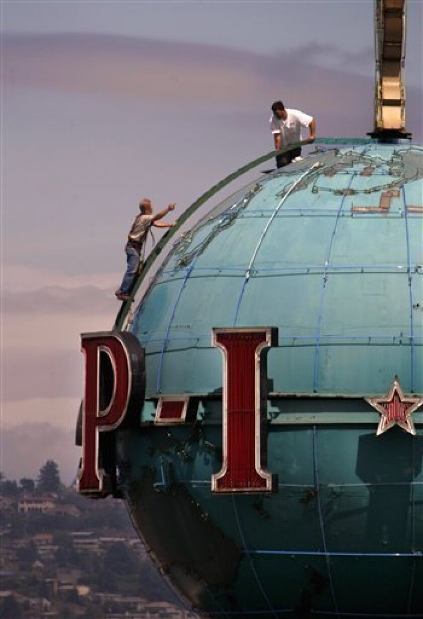 In this Thursday, June 30, 2005 file photo, a pair of workers stand atop the landmark globe on the roof of the building housing the Seattle Post-Intelligencer during maintenance work, in Seattle. On Friday, Jan. 9, 2009, the Hearst Corp. put Seattle's oldest newspaper, the Seattle Post-Intelligenc
