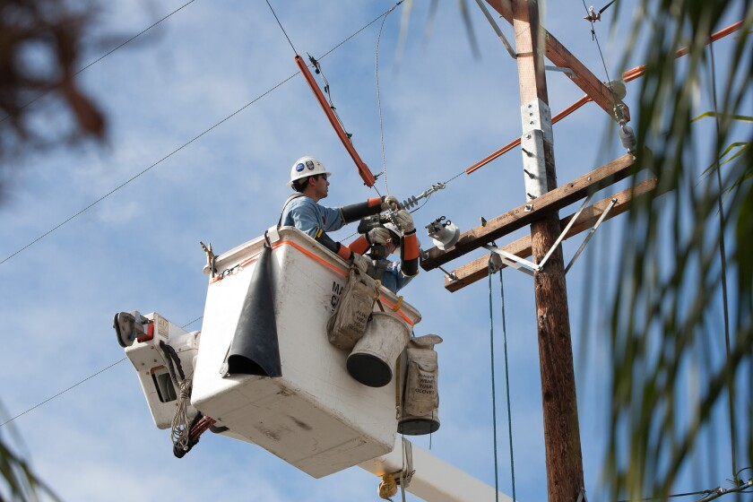 A San Diego Gas & Electric employee works on a power line. A 50-year-old franchise agreement between SDG&E and the city of San Diego expires in January 2021.