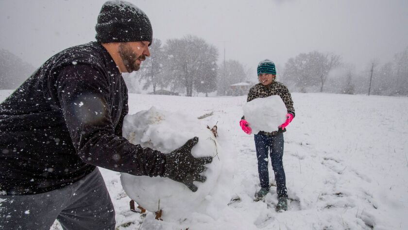 Stephen Fanning and his daughter Addison Fanning build a snowman during the heavy snow fall in Clant